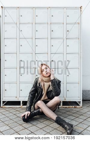 Fashion portrait of serious young blonde lady sitting near safes. Looking at camera holding cigarette.