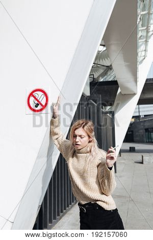 Fashion portrait of serious young blonde lady with cigarette outdoors. Looking aside.