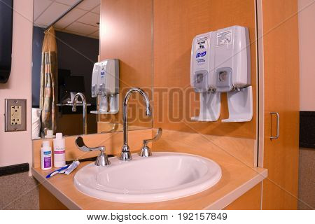 UNITED STATES - June 19, 2017: Sink in a hospital room with hand sanitizer and soap dispensers, and toiletries.