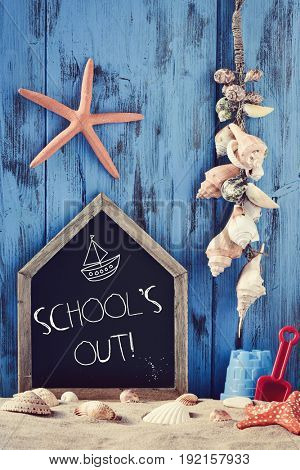 a house-shaped chalkboard with the text schools out surrounded by different beach toys, seashells and starfishes on the sand, against a rustic blue wooden background