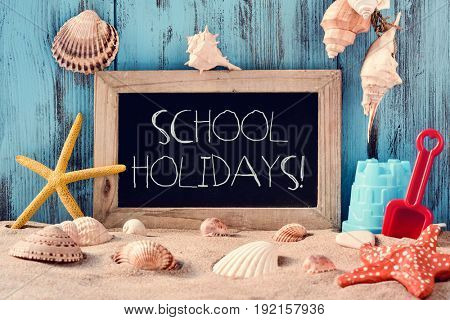 a wooden-framed chalkboard with the text school holidays surrounded by different beach toys, seashells and starfishes on the sand, against a rustic blue wooden background