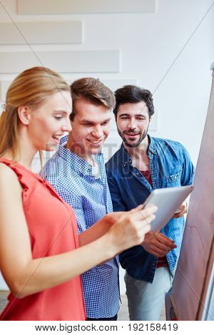 Start-up team during business meeting amazed by E-Mail on tablet