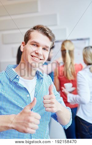 Young student as founder of a start-up holding happily thumbs up