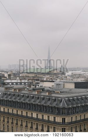 Aerial View Of Paris. Paris Skyline With Roofs And The Eiffel Tower On A Foggy Day. Panorama From Th