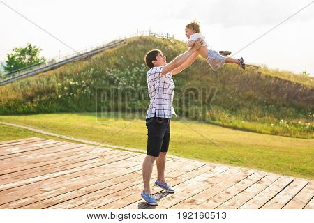 happy father holding little kid in arms, throwing baby in air. concept of happy family, fatherhood.