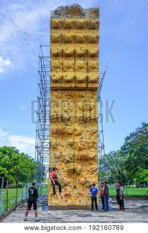 Labuan,Malaysia-May 21,2017:Adventure group of climber with safety equipment climb on climbing wall in Labuan,Malaysia.It is an activity in which participants climb up or across artificial rock walls