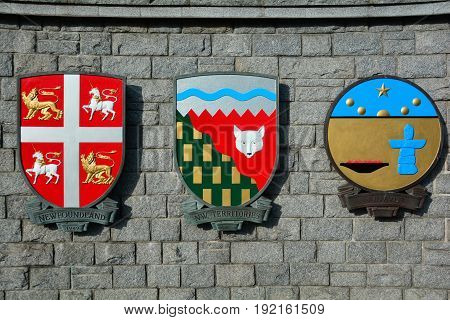 Victoria BC,Canada,January 23rd 2017.Coats of arms for the province of Newfoundland and the Northwest Territories and Nunavut hang from a stone wall in Victoria BC,Canada.