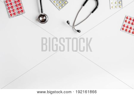 Medical equipment with stethoscope and pills in doctor's office in hospital on white desk background top view mock-up
