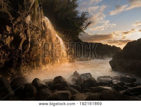 Setting sun at sunset illuminates a small waterfall falling into the ocean