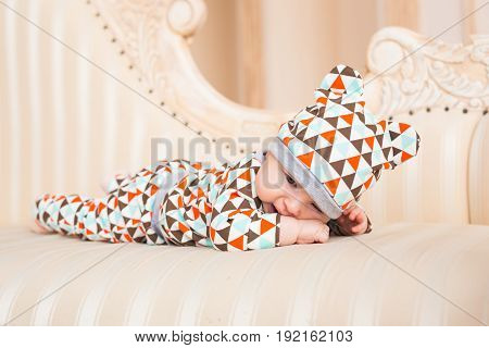 Baby, childhood and newborn concept - little child lying on the couch in the coloured cap