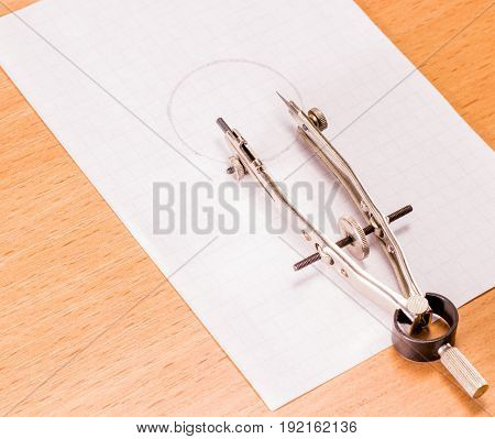 Compass on a sheet with a circle on a wooden background tool for students of school children and engineers