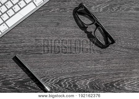 accountant work desk with glasses and keyboard for online payment on dark background top view space for text