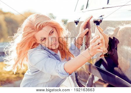 Young woman cleaning his car outdoors.Woman with a microfiber wipe the car polishing.