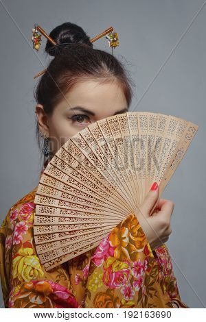 Pretty asian girl in kimono with fan posing over grey background