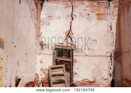 Weathered Old Abandoned brick wall with wooden window frame