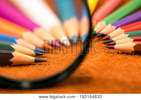 Colored pencils under the magnifying glass at a light brown background close-up