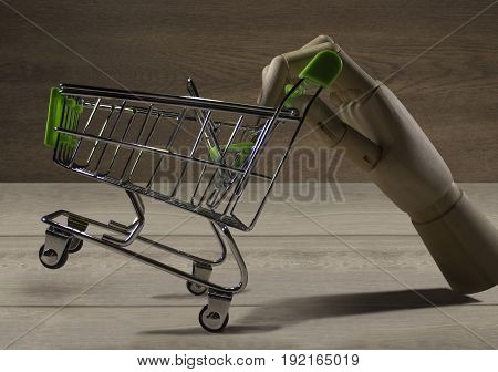Wooden hand with shopping cart. Hand of a wooden puppet holding an empty shopping cart photo.