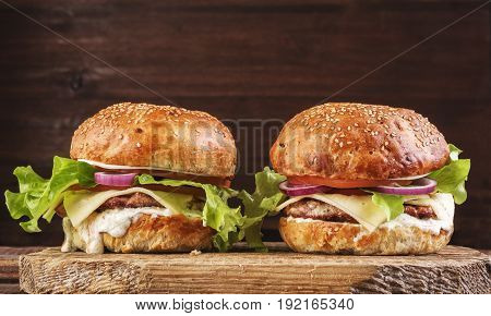Delicious Burgers On Wooden Cutting Board.