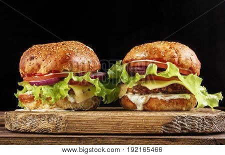 Homemade Burgers On Wooden Plate Isolated On Black Background
