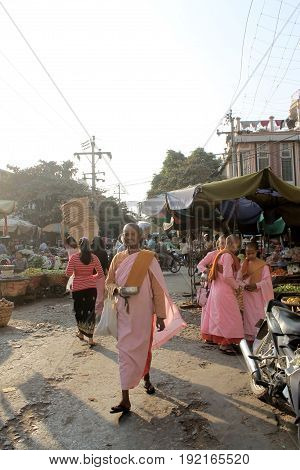 ZEGYO MARKET/MANDALAY, MYANMAR JAN 22: Buddhist nuns of different age in their typical pink and orange robes are colleting alms. January 22, 2016, Zegyo Market, Mandalay.