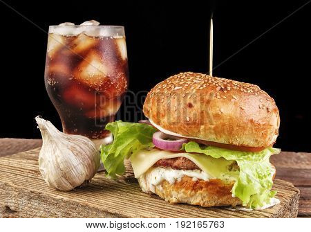 Homemade burger with beef patty, lettuce, tomato, cheese and red onion served with garlic, white sauce and ketchup, on wooden cutting board. With mug of cola with ice