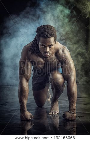 Handsome young muscular black man shirtless ready to sprint and run. On dark background with smoke