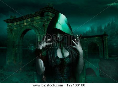 Beautiful sexy sorceress in green cloak holding antique watch on night nature background photo.