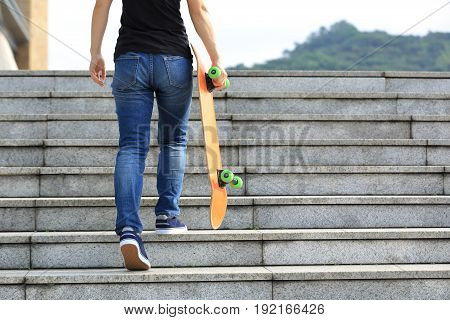 closeup of skateboarder take skateboard walking upstairs at city