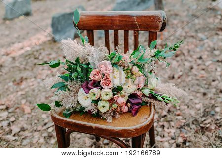 Beautiful wedding bouquet on an old brown chair standing outside. Horisontal