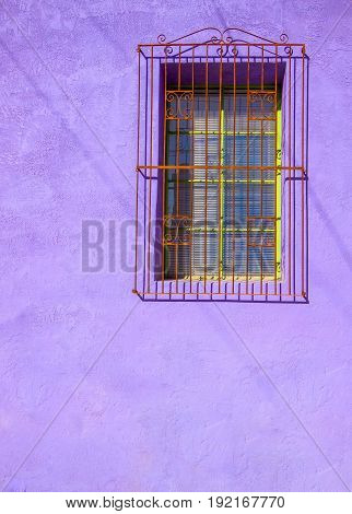 Painted Purple Stucco Wall with Barred Window and Shadow