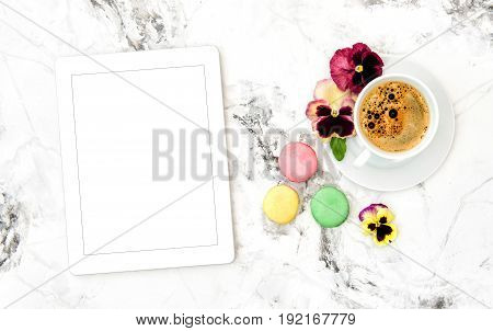 Coffee french cookies macaroons tablet PC pansy flowers. Floral flat lay