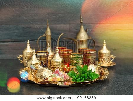 Oriental tea coffee table golden dishes with delight and mint. Ramadan kareem. Vintage style toned picture with light leaks