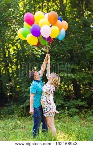 young couple man and his pregnant wife with balloons outdoors.