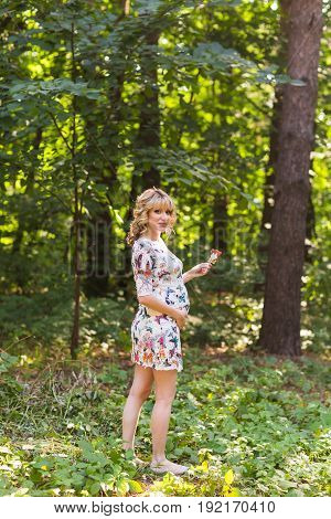 Full length portrait of young pregnant woman holding a lollipop in summer nature.