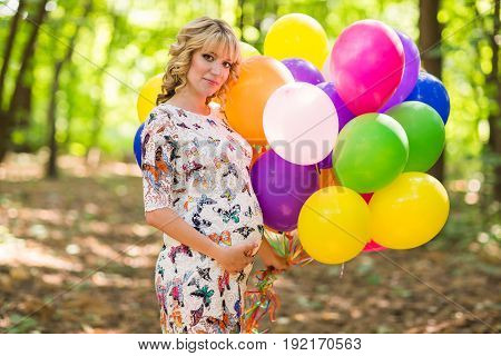 Young pregnant woman holding colorful balloons outdoors.