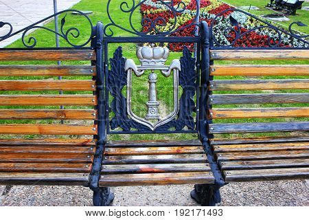 Part of the bench in the park, against the background of the flower bed