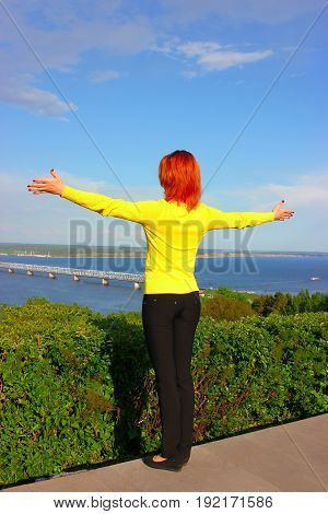 Rear view of a happy woman enjoying freedom of leisure and vacation. A woman raises her hands to a beautiful landscape. Summer happiness and leisure.