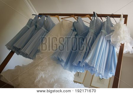 8 dresses in a row on a hanging from a 4 poster bed