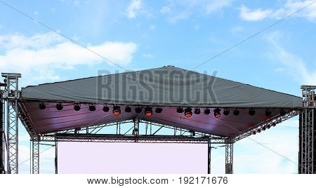 Part Illuminated blank concert stage, against a blue summer sky background