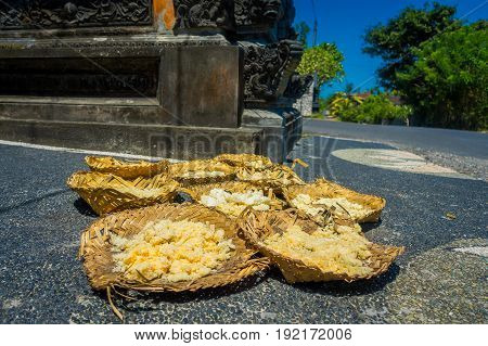 Cooked rice on a hat made of dry leafs in the ground in Denpasar city in Bali, Indonesia.