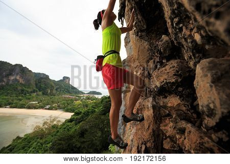 woman rock climber climbing at seaside cliff