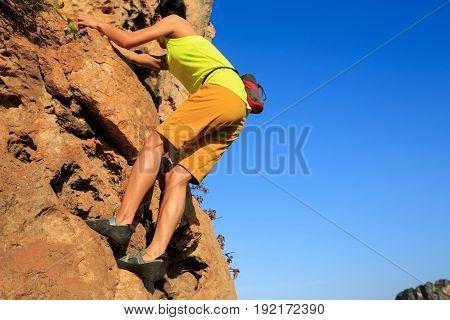 young woman rock climber climbing at cliff