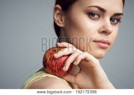 Woman with apple, woman holding an apple on her shoulder, diet, healthy food on a gray background.