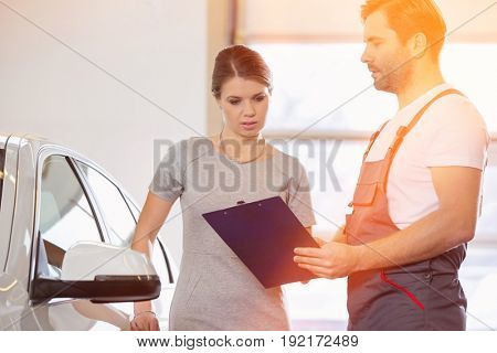 Repairman holding clipboard while conversing with female customer in repair shop