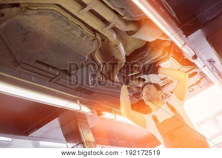 Low angle view of male automobile mechanic repairing car in repair shop