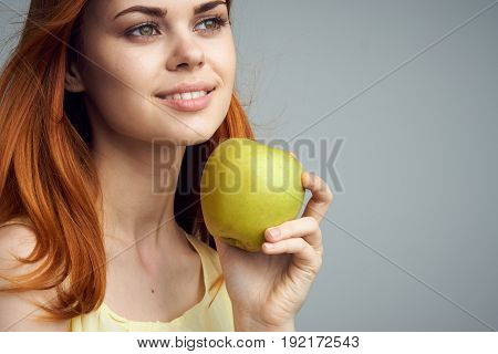 Woman holding an apple, diet, healthy food, woman with an apple on a gray background.
