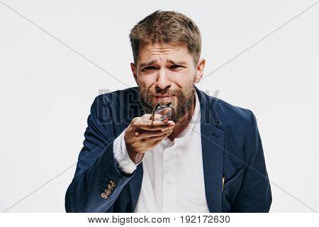 Businessman squinting, businessman holding glasses, businessman on light background.
