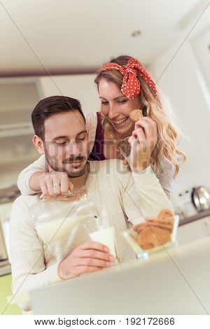 Young couple having breakfast at home in the kitchen.