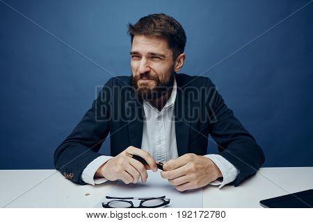 Businessman squinting, businessman holding a pen, businessman behind a workstation on a blue background.