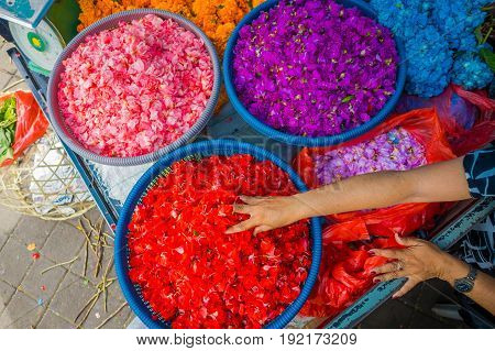 BALI, INDONESIA - MARCH 08, 2017: Outdoor Bali flower market. Flowers are used daily by Balinese Hindus as symbolic offerings at temples, inside of colorful baskets.